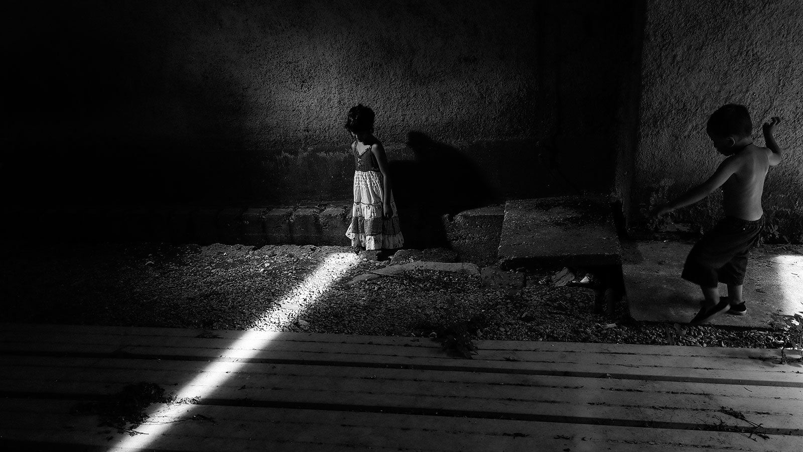 Young gypsy child stands in a shaft of light
